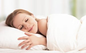 young beautiful woman sleeping and smiles in his sleep in bed